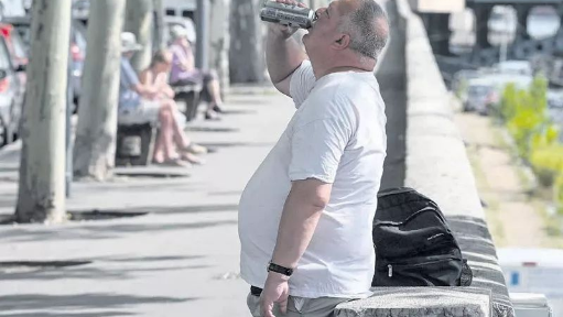 巴黎塞纳河边喝啤酒消暑的男子